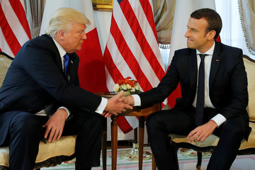 U.S. President Trump and French President Macron shake hands before a working lunch ahead of a NATO Summit in Brussels