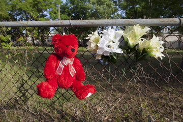 Teddy bear and flowers are left on a fence near the spot where Walter Scott was shot in North Charleston