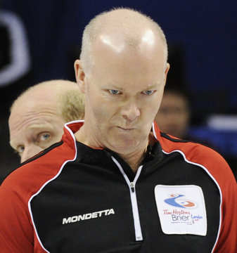 Ontario skip Howard lines up a shot as Alberta skip Martin looks on during their page playoff game at the Brier curling championships in London