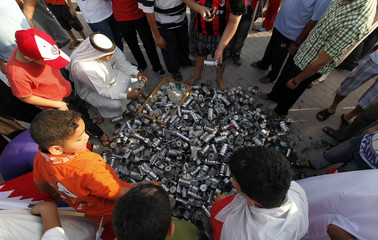 People look at tear gas and percussion grenade canisters displayed at a rally held by Bahrain's main opposition al-Wefaq party in Budaiya