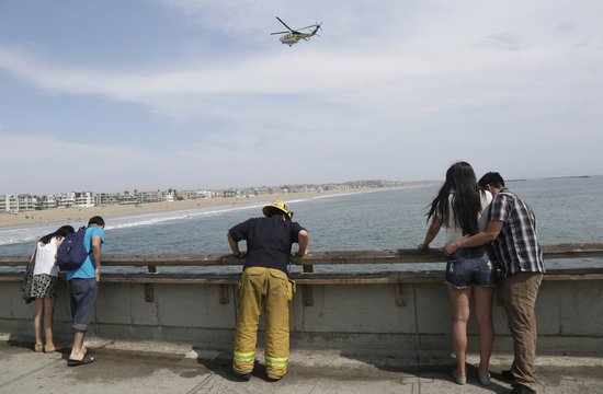 Firefighter looks over the pier during a search for victims of a lightning strike that injured people in Venice, California
