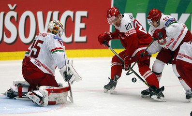Denmark's Madsen fights for the puck with Usenko of Belarus as goaltender Lalande looks on during their Ice Hockey World Championship game at the CEZ arena in Ostrava