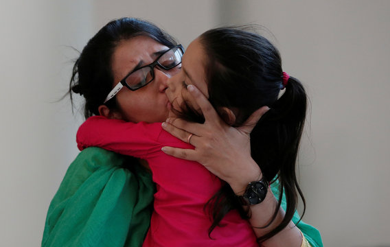 Uzma, an Indian woman who according to local media was forced to marry a Pakistani man, kisses her daughter after her arrival, in New Delhi