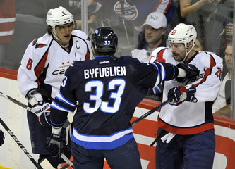 Winnipeg Jets' Dustin Byfuglien pushes Washington Capitals' Alex Ovechkin and Troy Brouwer during the first period of their NHL game in Winnipeg