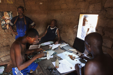 Butterfly wing artists make mosaics at a house in Bangui
