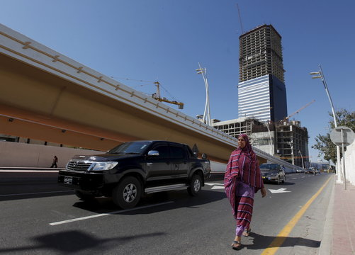 The construction site of the Bharia Icon 62 story building is seen in the background as a woman walks along a street in Karachi