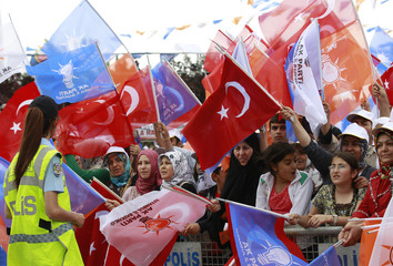 Supporters of Justice and Development Party wave Turkish and party flags as they wait for arrival of Erdogan during an election rally in Istanbul
