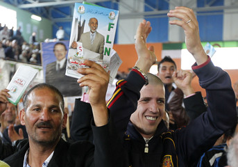 A supporter of the National Liberation Front party holds up a flyer with an image of party leader Abdelaziz Belkhadem during his parliamentary election campaign rally in Algiers