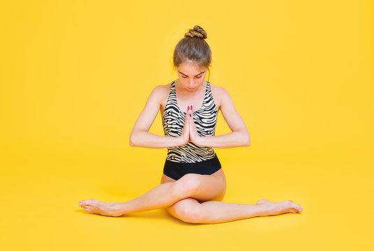 Young fit woman gymnast stretching isolated on yellow background