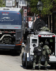 A passenger walks away from a Greyhound bus with his hands in the air as a SWAT team surround the bus after a call that there might be a bomb on board in Portsmouth