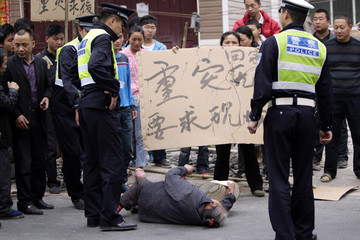 Survivor falls to ground during protest by villagers against lack of rescue operations after Saturday's earthquake, at Chaoyang village in Lushan county of Ya'an