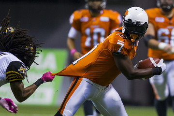 B.C Lions WR Hawkins is tackled by Hamilton Tiger-Cats DB Murray during the first half of their CFL football game in Vancouver
