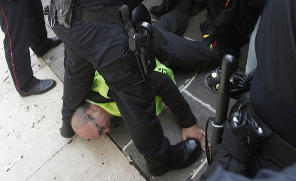 A protestor is seen lying on the floor as a group of retirees calling themselves iaioflautas confront the police in front of Generalitat de Catalunya palace in Barcelona