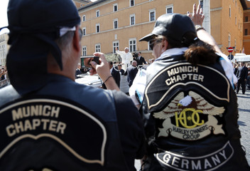 A Harley-Davidson biker takes a picture of Pope Francis in Rome