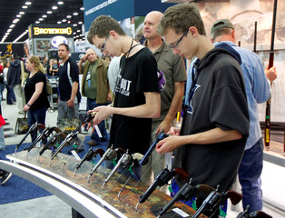 Gun enthusiasts look over Benelli USA guns at the National Rifle Association's annual meetings & exhibits show in Louisville