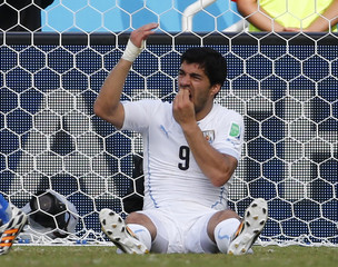 Uruguay's Luis Suarez holds his teeth during the 2014 World Cup Group D soccer match between Uruguay and Italy at the Dunas arena