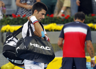 Djokovic of Serbia walks away after his defeat to Tipsarevic of Serbia during their men's quarter-final match at the Madrid Open tennis tournament