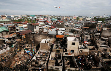 A Philippine Airlines passenger plane takes off at Ninoy Aquino International airport near a residential neighbourhood raized by a fire in Paranaque, Metro Manila