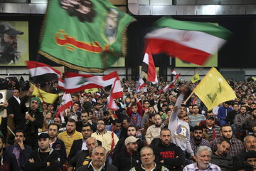 Yemeni and Lebanese Hezbollah supporters carry Yemeni, Lebanese, Hezbollah, religious and Iranian flags during a speech by Lebanon's Hezbollah leader Nasrallah against U.S.-Saudi aggression in Yemen, in Beirut's southern suburbs