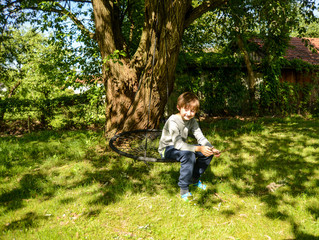 Boy sitting on a swing by a tree smiling