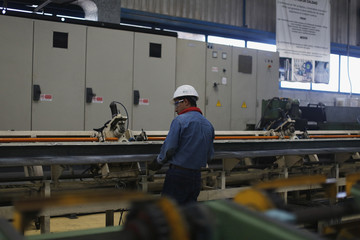 Worker checks machinery at TIM stainless steel wire factory in Huamantla