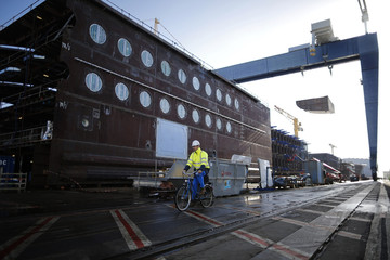 A ship builder cycles past a section of the Oasis Class 3 cruise ship under construction at the STX Les Chantiers de l'Atlantique shipyard site in Saint-Nazaire