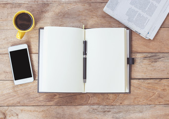 Open notebook with cup of coffee,newspaper.