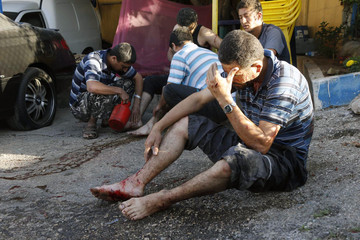 Two wounded men are treated by their friends after two rockets hit their houses in Beirut