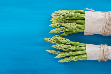 Bunches of green and white asparagus on a blue wooden background top view