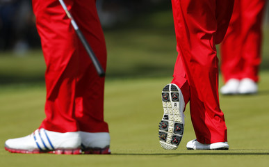 Woods' logo is seen on the bottom of his shoe as he stands with Johnson on the 14th green during a practice round at the 39th Ryder Cup golf matches at the Medinah Country Club