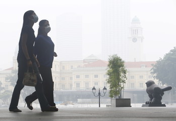 Office workers wearing masks walk during lunch hour at the central business district in Singapore
