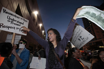 Woman waves a replica 100 dollar bill at an Occupy LA march in Los Angeles
