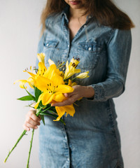 Vibrant yellow lilies in woman hand. Spring or summer concept