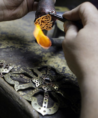 A jewellery maker works on a pendant designed from a verse in the Muslim Koran, as well as other designs based on the Christian Cross, in a workshop in Cairo