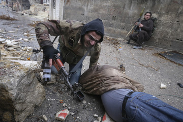 A Syrian rebel helps evacuate his comrade after the group is hit by sniper fire as they prepared to attack a government controlled army checkpoint in the Ain Tarma neighborhood of Damascus, Syria