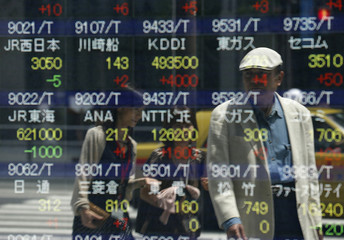A man is reflected on a stock index board as he watches it outside a brokerage in Tokyo