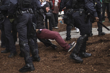 A protester demanding justice for Michael Brown is detained by police in riot gear for disrupting traffic in St. Louis