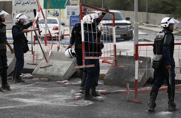 Riot police officers remove roadblocks set-up by protesters during an anti-government demonstration in Karrana
