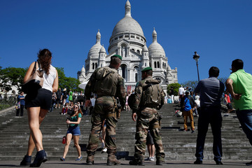French soldiers patrol as tourists visit Montmartre's Sacre Coeur Church in Paris