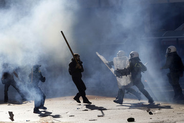Masked youths clash with riot policemen during riots in Athens