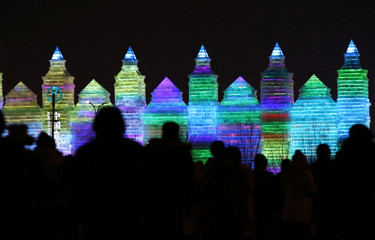 People heading to 31st Harbin International Ice and Snow Festival venue are silhouetted against ice sculptures illuminated by coloured lights at opening day in northern city of Harbin