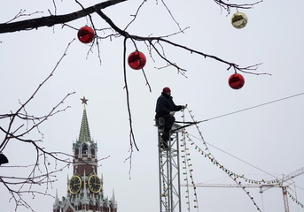 A worker removes Christmas decorations in Red Square, with the Spasskaya Tower of the Kremlin seen in the background, in central Moscow, Russia