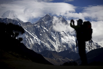 A tourist is silhouetted as he takes pictures of Mount Nuptse as Mount Everest is covered with clouds in Solukhumbu district, also known as the Everest region