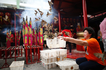 A woman releases birds for good luck during Lunar New Year celebrations at Dharma Bhakti temple in Jakarta