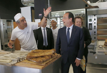 French President Hollande reacts with teacher in a bakery classroom who prepares baguettes during a tour devoted to training and professional integration of young people in Paris