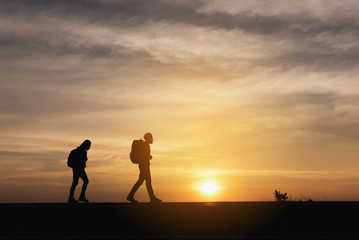 Silhouette of the Couple walking on the road near the sea. Family travel and healthy lifestyle concept.