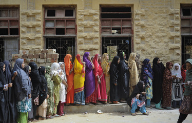 Women line up to receive money from  a charity organization at an assistance center setup at  in Karachi