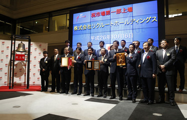 Recruit Holdings President and CEO Minegishi poses for a photograph with his company's executives and President of Tokyo Stock Exchange Kiyota after ringing a bell during a ceremony to mark the company's debut on the Tokyo Stock Exchange in Tokyo