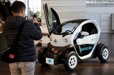 A visitor takes a photo of Nissan New Mobility Concept car in the showroom at the carmaker's headquarters in Yokohama