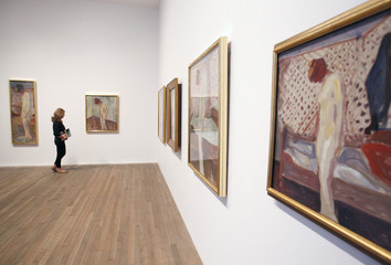"""Ward of the Tate poses with all six paintings of Edvard Munch's """"Weeping Woman"""" series at the Tate Modern in London's Southbank"""